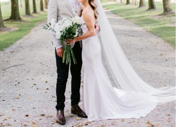 a bride and groom standing together on their wedding day. The bride is wearing a beautiful wedding dress and holding a white bouquet of flowers.