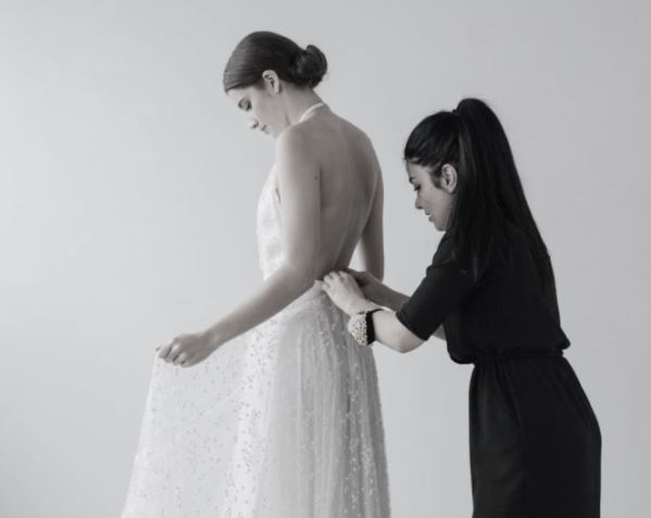 a bride having her wedding dress altered at Kenny & Harlow's Auckland boutique.